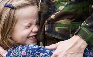 Child embracing military member
